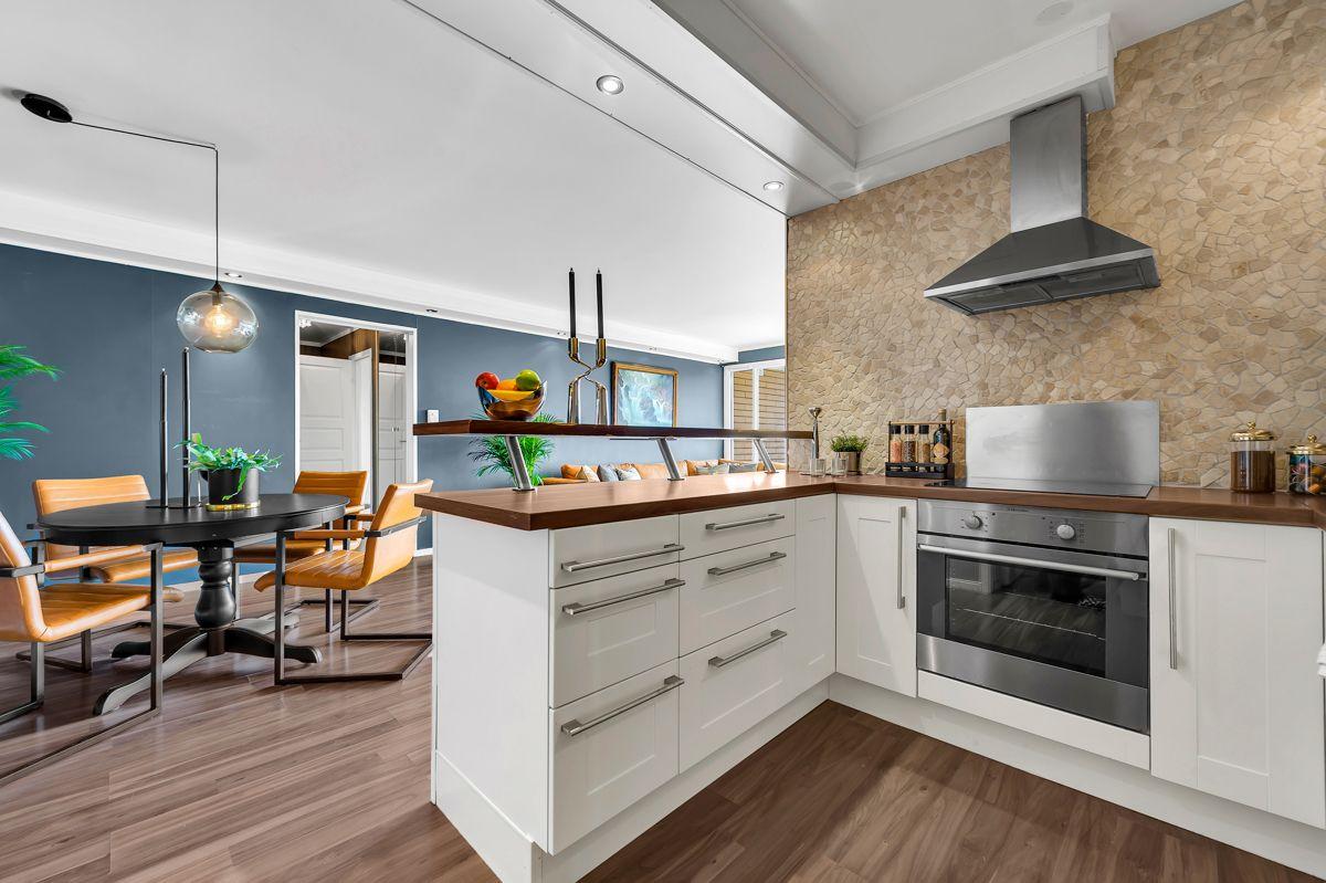 Myrehagen 23 Stilrent kjøkken som har innredning med hvite og profilerte fronter, samt benkeplater i laminat.