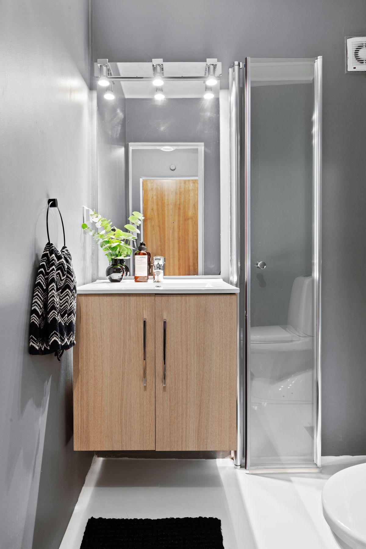 Thunes vei 4 B Baderommet inneholder dusjhjørne med to dusjhoder, toalett, servantskap og speil.