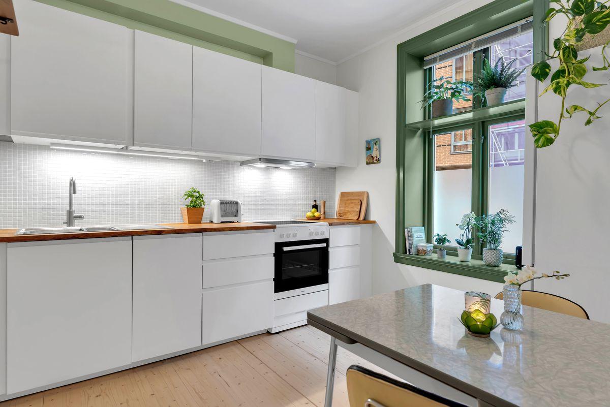 Urtegata 45 Stilrent og lekkert kjøkken som har innredning fra 2018 med hvite og glatte fronter, samt benkeplate i heltre.