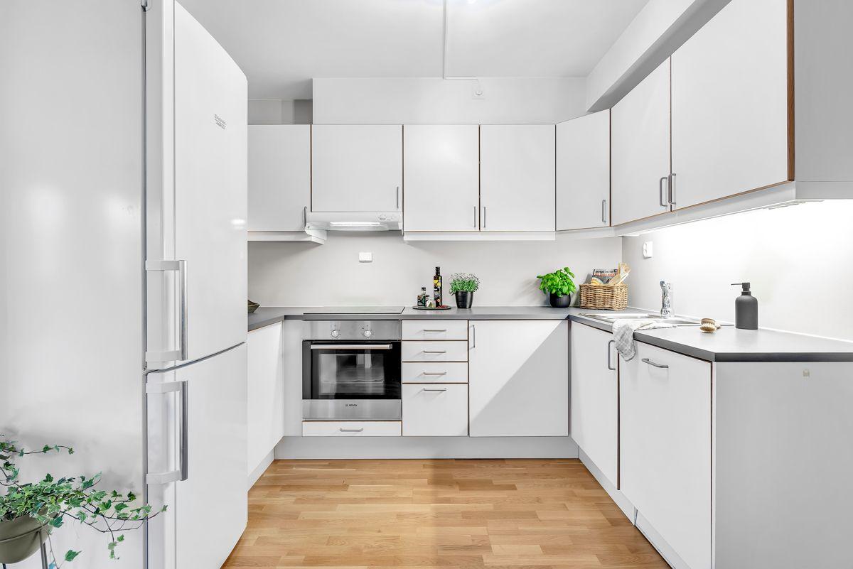 Arnljot Gellines vei 5A Stilrent og tidløst kjøkken som har innredning med hvite og slette fronter, samt benkeplate av laminat.