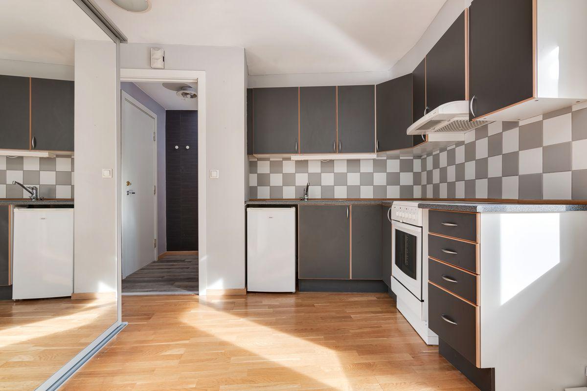 Enebakkveien 15 Kjøkkenet har innredning med slette og grå fronter, samt laminert benkeplate med nedsenket oppvaskkum.