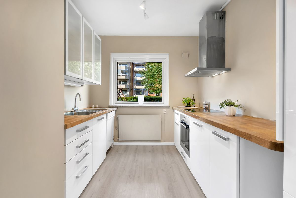 Karl Staaffs vei 51 Tidløst kjøkken som ble montert i 2019 som har innredning med lyse og glatte fronter, tre vitrineskap, samt benkeplate i heltre.