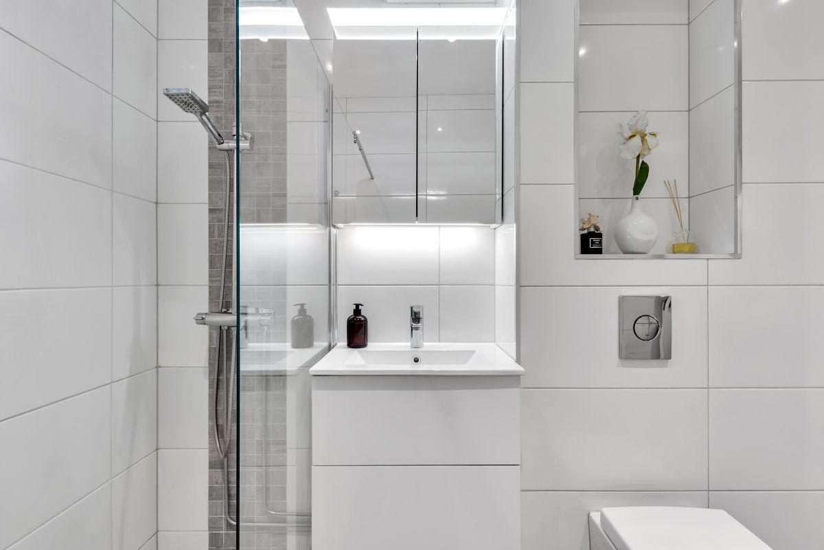 Karl Staaffs vei 51 Baderommet inneholder dusjhjørne med glassvegg, hånddusj og regnfalldusj, vegghengt toalett, samt servantskap.