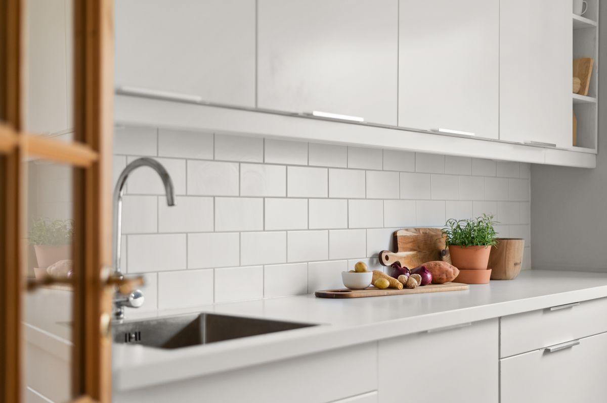 Ålesundgata 3 A Moderne og stilren kjøkkeninnredning som var ny i 2013. Du har god skap- og benkeplass i innredningen som har hvite glatte fronter og hvit laminert benkeplate med nedfelt oppvaskkum.