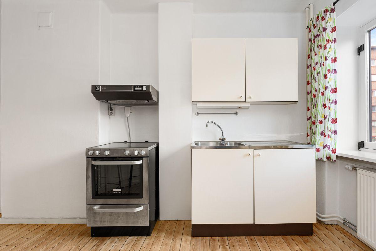 Bentsegata 17 Eldre kjøkkeninnredning fra Norema med hvite glatte fronter, laminert benkeplate og benkebeslag med oppvaskkum.