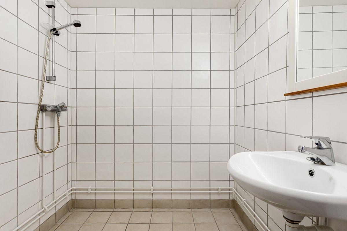 Bentsegata 17 Baderommet er utstyrt med vegghengt servant med speil over, dusjhjørne med forheng og gulvmontert toalett.
