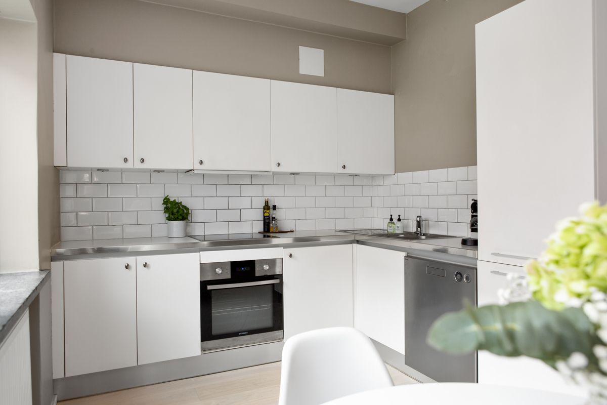 Carl Jeppesens gate 24 Moderne og tidløst kjøkken med hvite glatte fronter og laminert benkeplate med nedsenket oppvaskkum. Praktisk med fliser i benkeryggen og belysning under overskapene.
