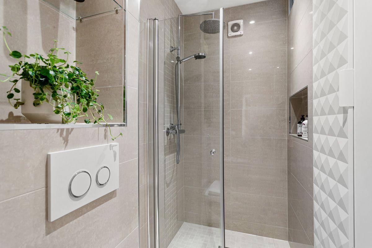 Erika Nissens gate 7 Romslig nedsenket dusjsone med glassdør, mosaikkfliser, innebygget hylle for såper og både hånd- og regnfallsdusj.