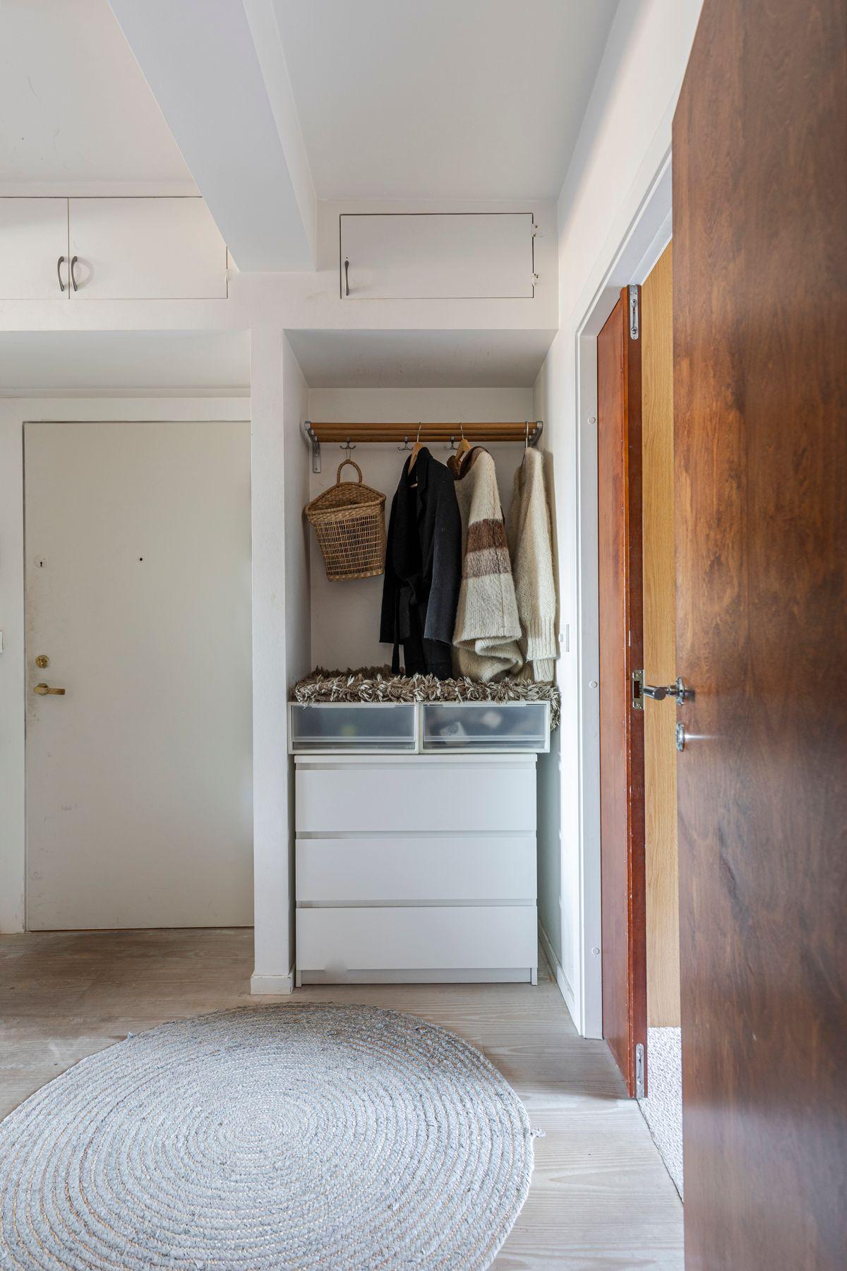 Brinken 16D Innbydende entré med plass til oppbevaring av yttertøy og sko i åpen nisje med kleshengerstativ og plassbygde skap over, samt plassbygget skap i gang.