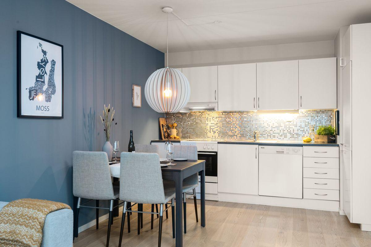 Sinsenveien 9 Stilren kjøkkeninnredning med hvite, slette fronter og mosaikkfliser over benkeplate.