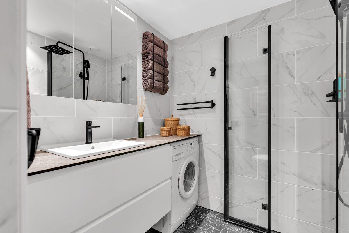 Martin Skatvedts vei 5B Baderomsinnredningen består av en stilren servantinnredning, servant, speilskap, vegghengt toalett og dusjhjørne med innfellbare glassdører.
