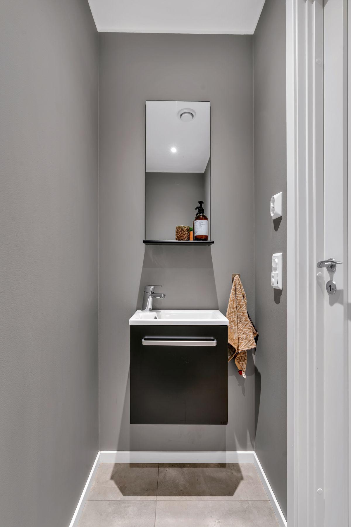 Hektnerhagan 164 Innredningen består av servant med skap under, speil på vegg og toalett.