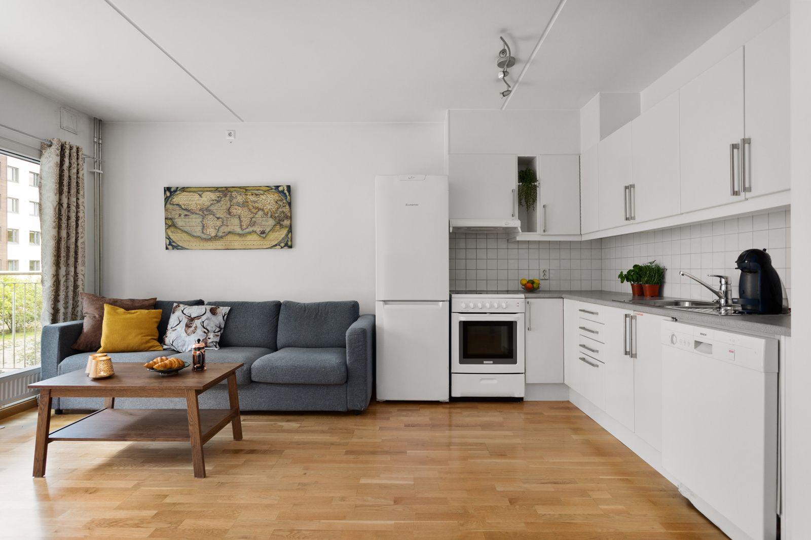 Nydalen allé 23 Åpen kjøkkenløsning mot stue. Kjøkkeninnredning med slette fronter. Benkeplate av laminat. Nedfelt oppvaskkum av rustfritt stål og ett-greps armatur fra Oras. Fliser på vegg over kjøkkenbenk.