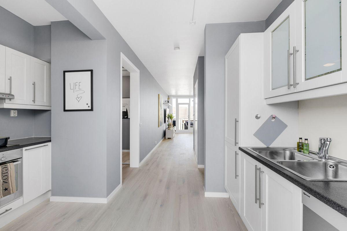 Gunnar Schjelderups vei 11L Moderne og pent kjøkken med god benk-/skapplass. Kjøkkeninnredning med hvite enkelt profilerte fronter, benkeplate i stein med kum og ett-greps blandebatteri.