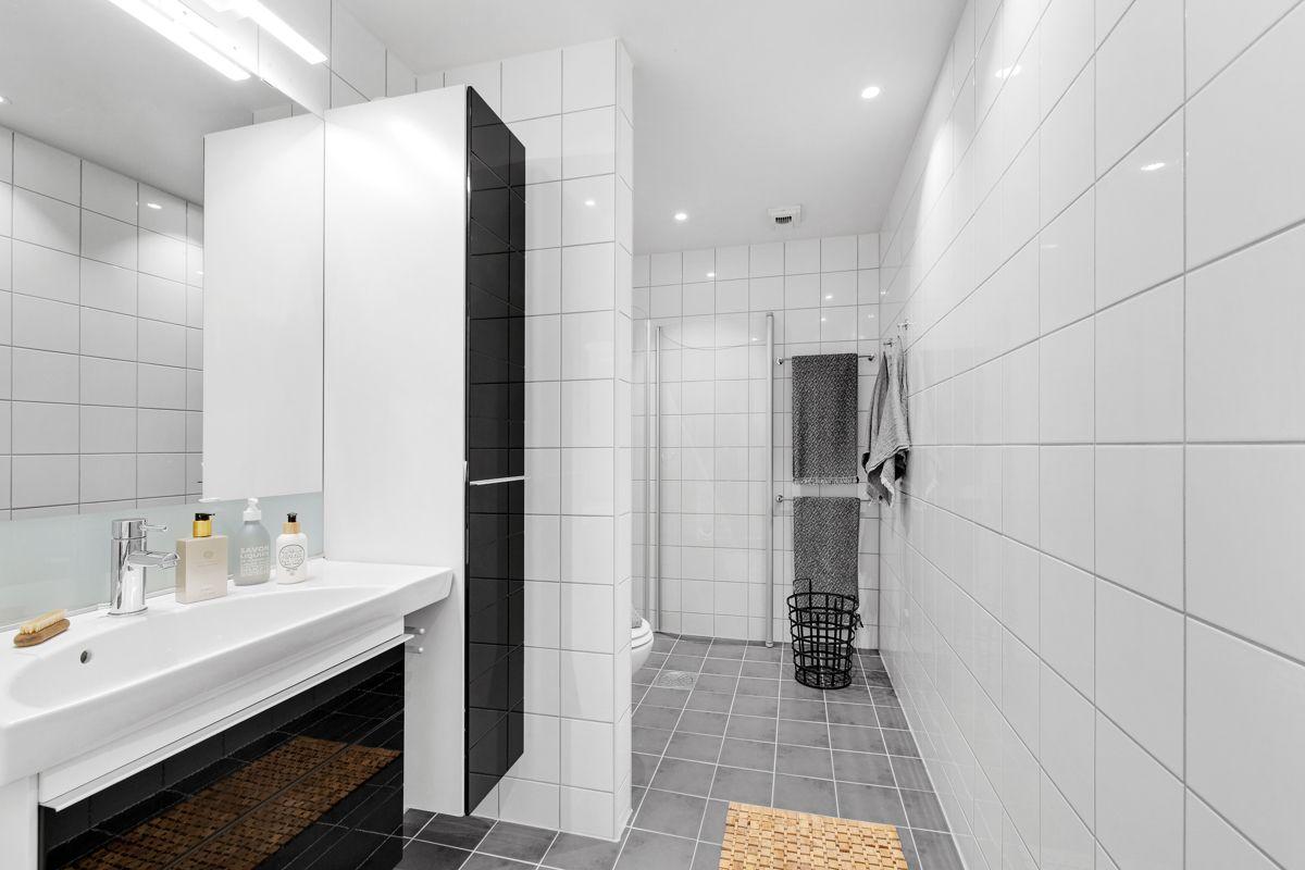 Gunnar Schjelderups vei 11L Lekkert og romslig flislagt bad med varmekabler i gulv. Delvis adskilt dusjnisje, og god plass til vaskemaskin.