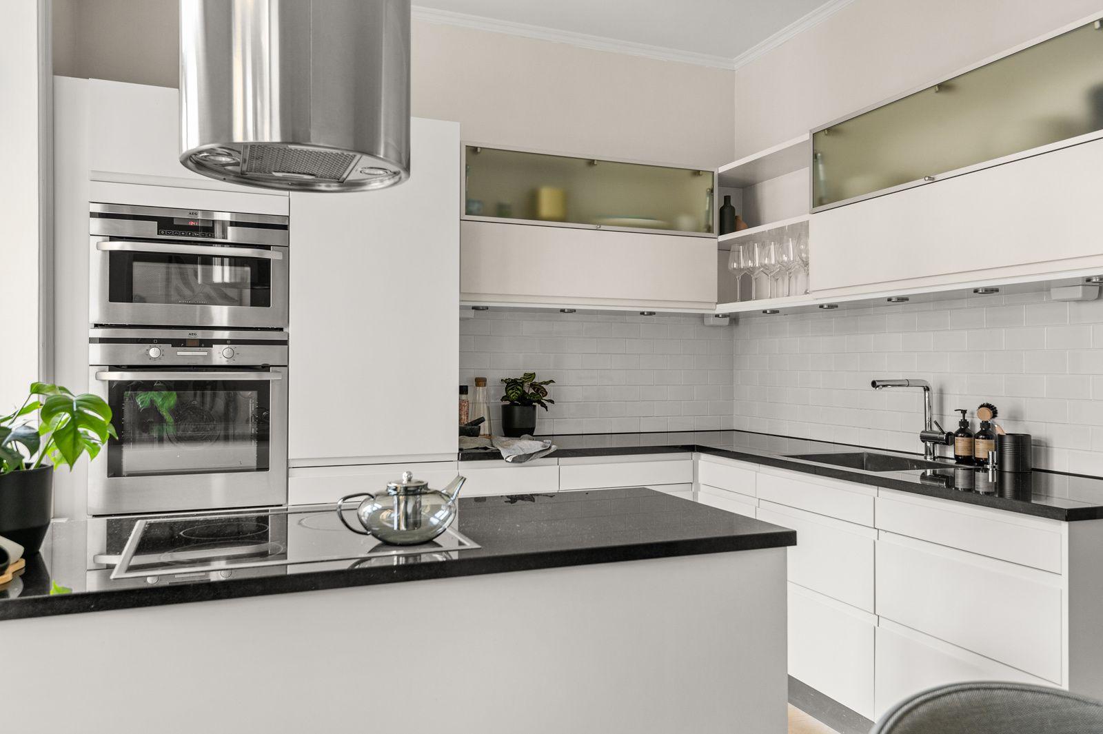 Paulus' plass 3 B Moderne innredning med hvite glatte fronter og påkostet benkeplate av stein med planlimt oppvaskkum.