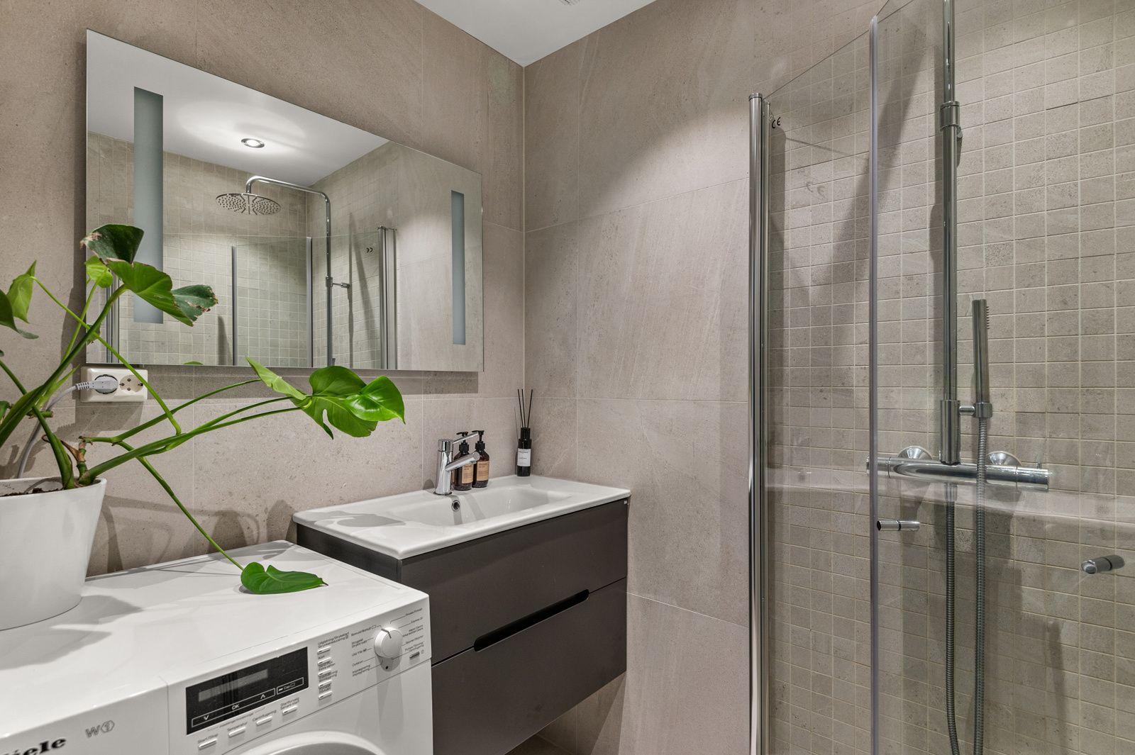 Paulus' plass 3 B Moderne baderomsinnredning med skuffer og heldekkende servant, speil med integrert belysning over. Plass og opplegg for vaskemaskin.